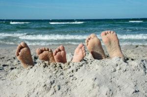Kinderfüße ragen aus dem Sand.
