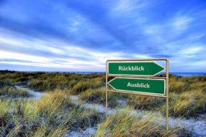 Ein Straßenschild in den Dünen verweist auf Vergangenheit und Zukunft.