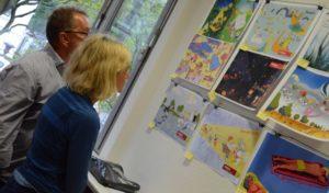 Dr. Maria Linsmann und Uli Mühlberger betrachten die Illustrationen.
