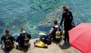 Taucher steigen von der Badeplattform des Hotels Kalura im Norden Siziliens ins Wasser
