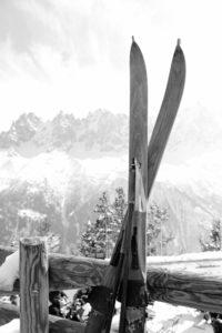 Holzski lehnen vor verschneiter Bergkulisse an einem Holzzaun