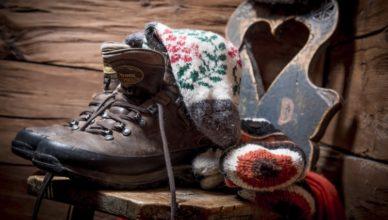 Ein paar Wanderschuhe mit Wollsocken stehen auf einem alten Holzstuhl
