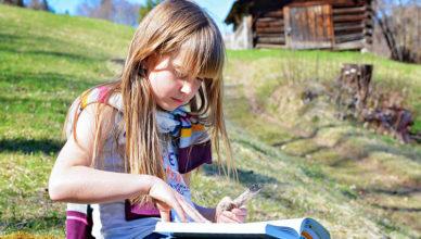 Ein Mädchen liest auf einer Bergwiese ein Buch.