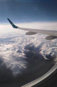 Der Blick aus dem Fenster eines Flugzeugs auf die Alpen.