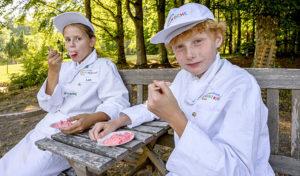 Vamos und Europa Miniköche: Kinder in Kochmontur probieren ein selbstgemachtes Dessert.