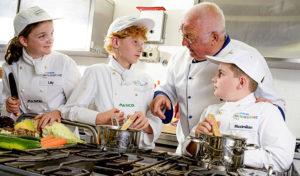 Vamos und Europa Miniköche: Der Koch Jürgen Mädger steht zusammen mit Kindern am Herd.