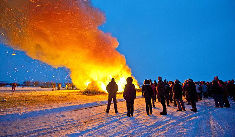 Biikebrennen auf Pellworm: In dicker Winterkleidung stehen die Menschen ums Feuer